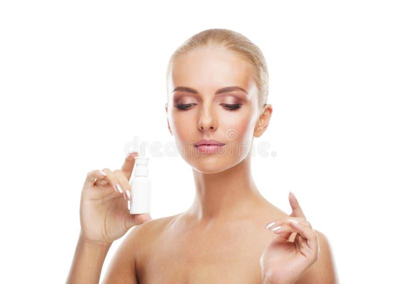 在白色隔绝的女孩使用nosal浪花湿剂的和下落 流鼻水、过敏、寒冷和流感病症,窦炎 免版税图库摄影