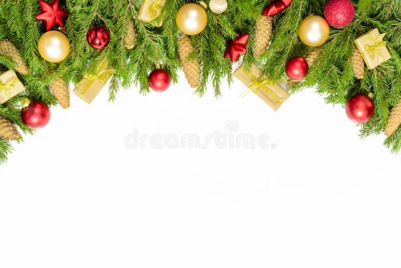 在白色隔绝的宽成拱形的圣诞节边界,由新鲜的冷杉分支和装饰品组成了在红色和金子 库存照片