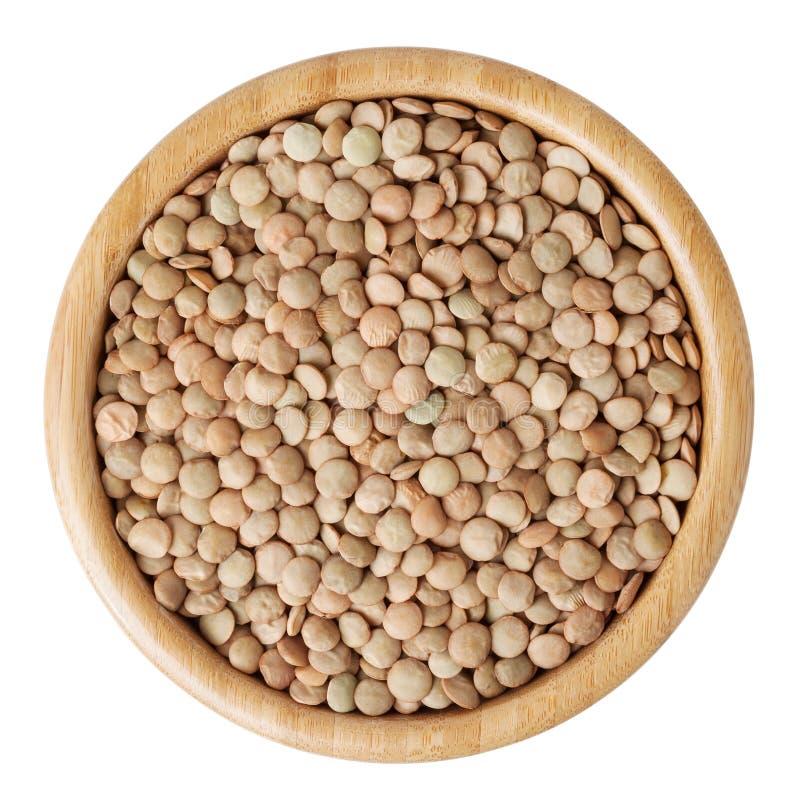 在白色隔绝的木碗的未煮过的扁豆 免版税库存图片