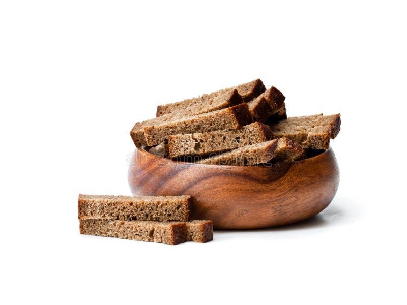 在白色隔绝的木碗的黑麦面包薄脆饼干 库存图片