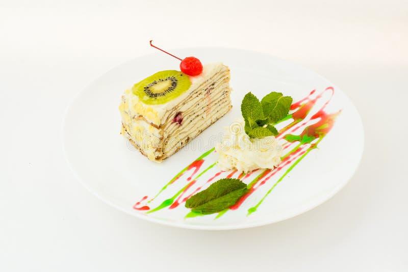在白色隔绝的板材的猕猴桃蛋糕 库存图片