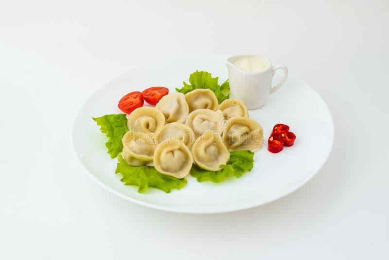 在白色隔绝的板材的饺子 免版税库存照片