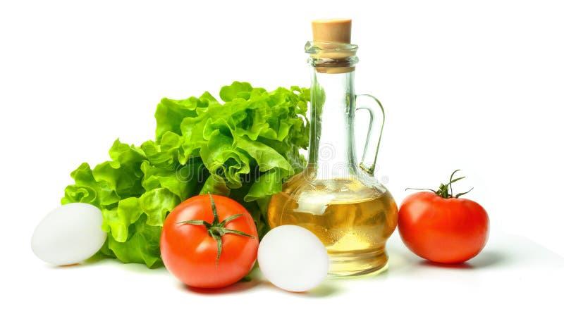 在白色隔绝的沙拉、蛋,蕃茄和菜油 明亮的饱和的颜色 免版税库存图片