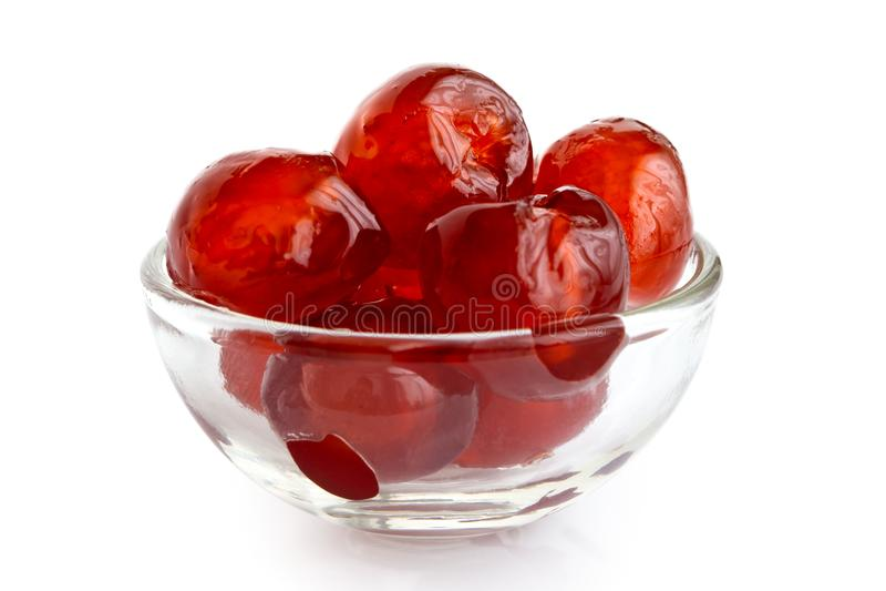 在白色隔绝的玻璃碗的红色糖渍的樱桃 库存照片