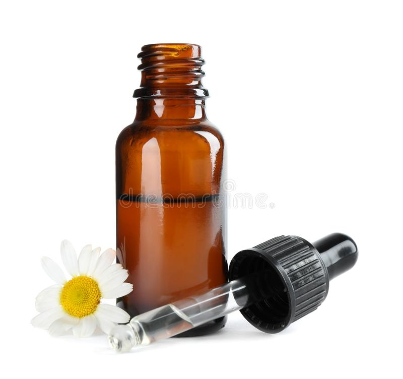 在白色隔绝的瓶草本精油、吸移管和花 免版税库存图片