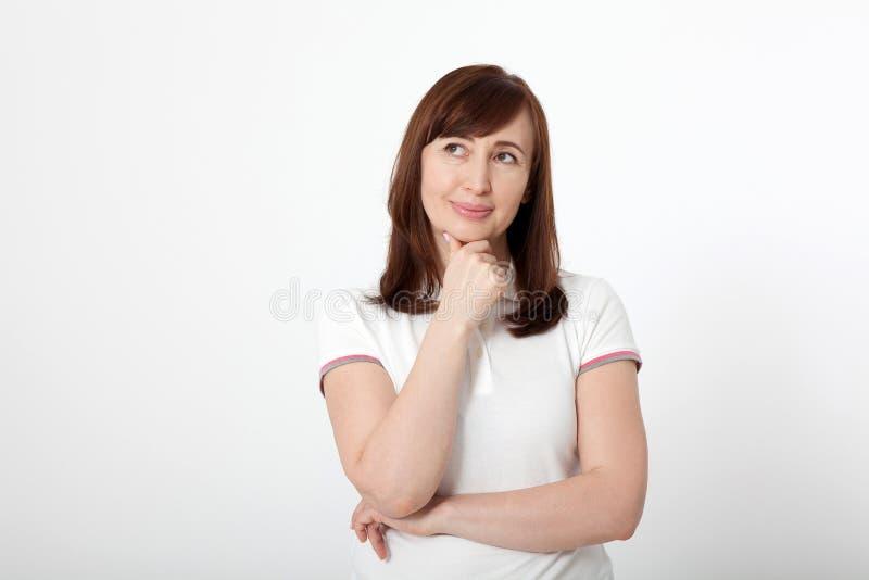 在白色隔绝的白色马球T恤杉的想法的中部年迈的妇女,复制空间 免版税库存图片
