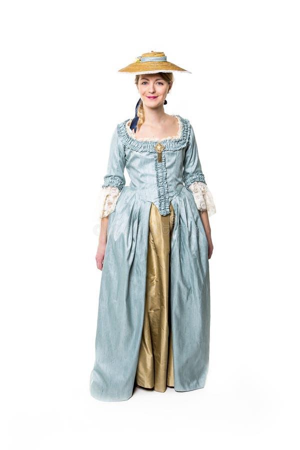 在白色隔绝的长的中世纪礼服的年轻美丽的妇女 库存照片