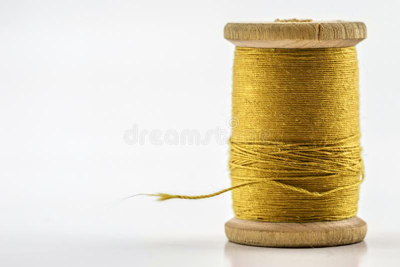 在白色隔绝的黄色缝合针线卷轴或短管轴  浅 免版税库存照片