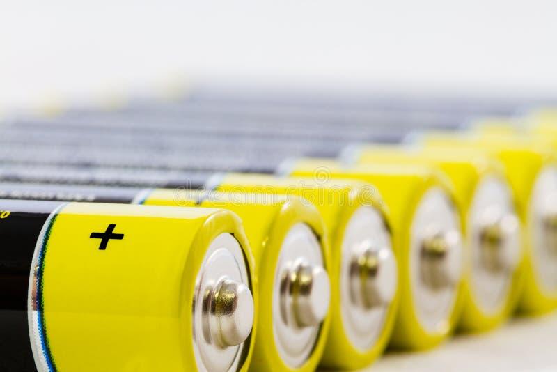 在白色隔绝的黄色黑色AAA碱性电池 免版税库存照片