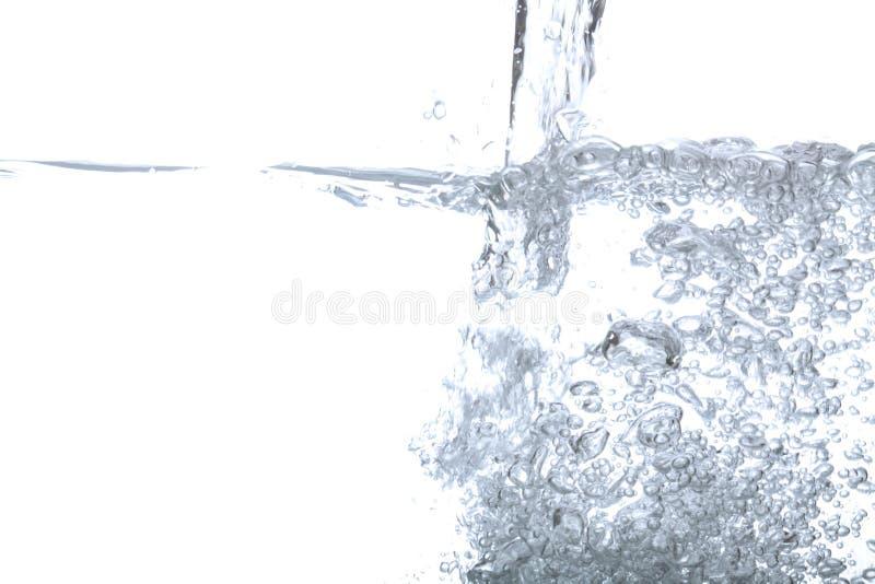 在白色隔绝的倾吐的饮用水和泡影空气 免版税图库摄影