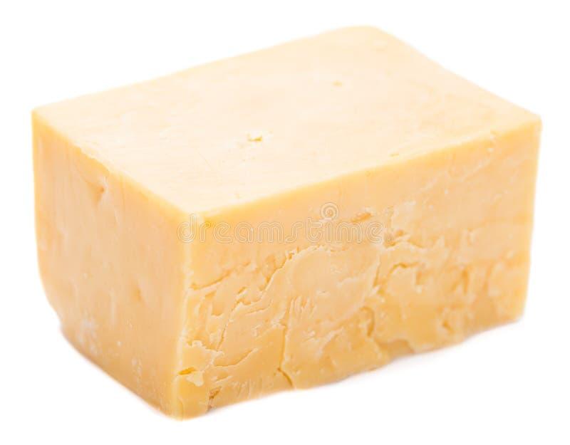 在白色隔绝的切成小方块的切达乳酪 库存图片