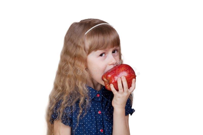 在白色隔绝的可爱的小女孩尖酸的红色苹果 图库摄影
