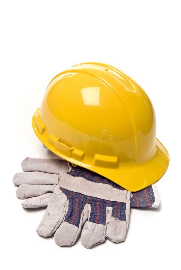 在白色隔绝的安全帽和工作手套 免版税库存图片