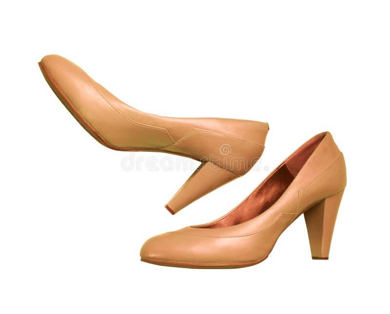 在白色隔绝的对米黄妇女` s高跟鞋 免版税库存图片