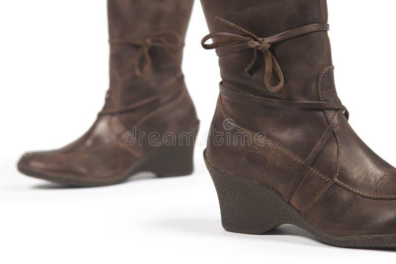 在白色隔绝的布朗女性皮靴 免版税库存照片