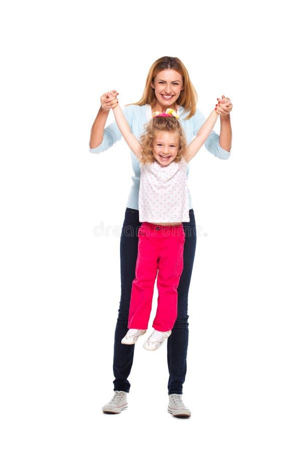 年轻在白色隔绝的母亲和她的小女儿 免版税库存照片