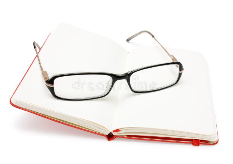 在白色隔绝的红色开放笔记本和玻璃 免版税库存图片