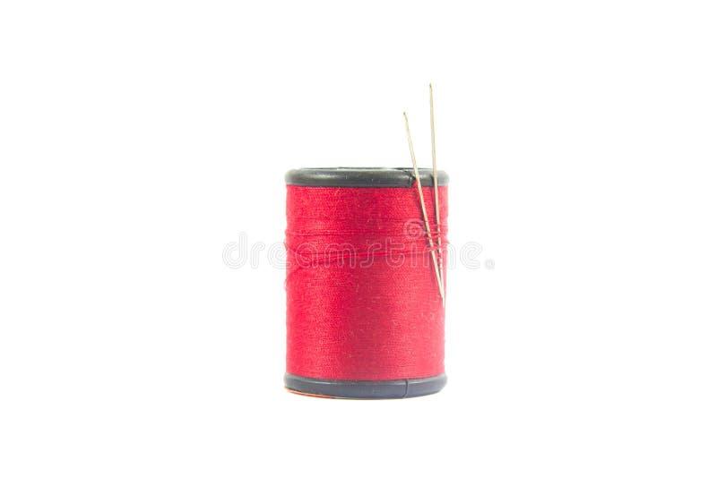 在白色隔绝的红色缝合针线卷轴或短管轴  背景 库存照片