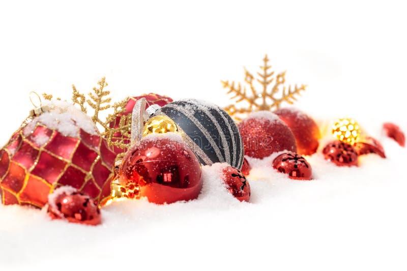 在白色隔绝的雪的许多圣诞节球 免版税库存图片