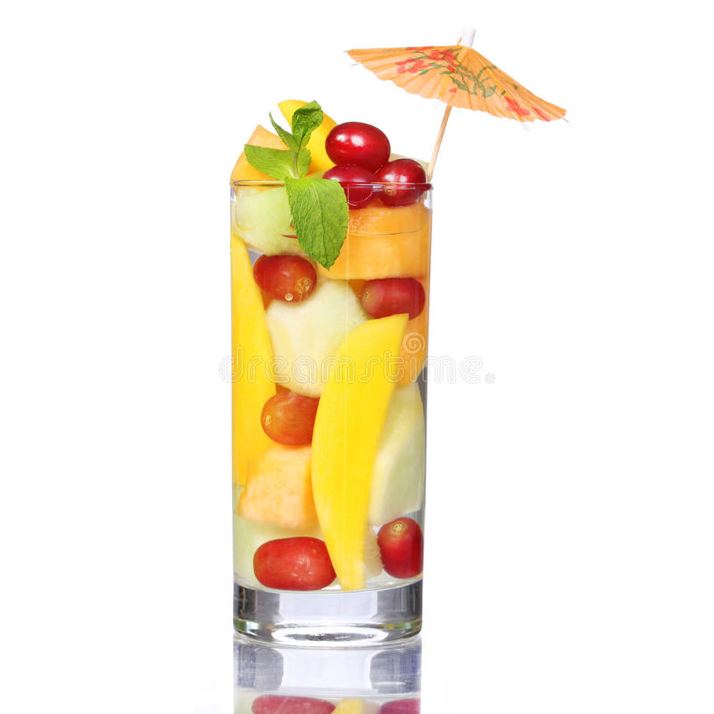 在白色隔绝的水果鸡尾酒。新切片芒果、瓜和葡萄在玻璃用薄菏和伞在上面。 免版税库存图片