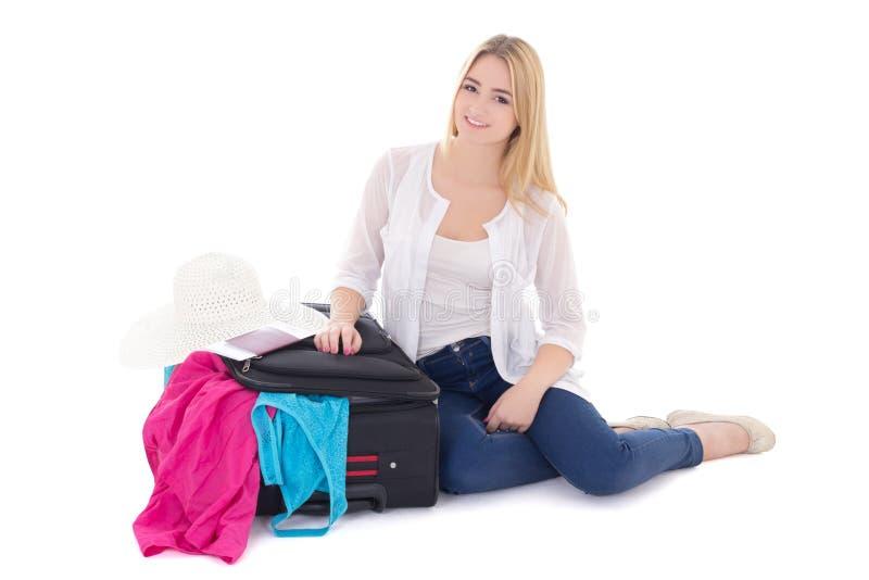在白色隔绝的年轻美丽的妇女包装手提箱 库存图片