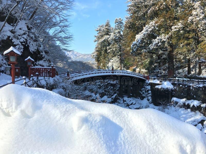 在白色雪下的Shinkyo红色桥梁在日光日本 免版税库存图片