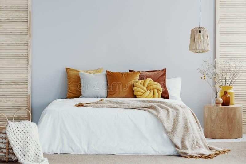 在白色鸭绒垫子的温暖的毯子在舒适卧室内部 免版税库存照片
