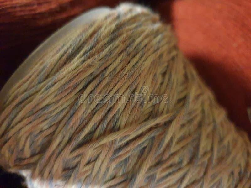 在白色,玫瑰色和浅兰的棉纱品在我的手工的一个锥体 在锥体的cottonthread 图库摄影