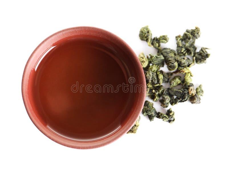 在白色,顶视图的杯领带观世音菩萨oolong和茶叶 免版税库存照片