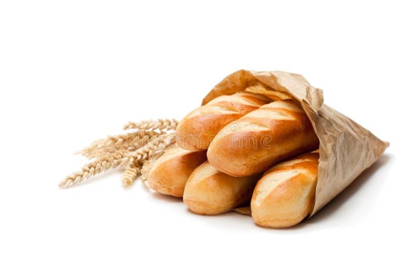 在白色b隔绝的纸袋和麦子耳朵的微型大面包面包 库存照片