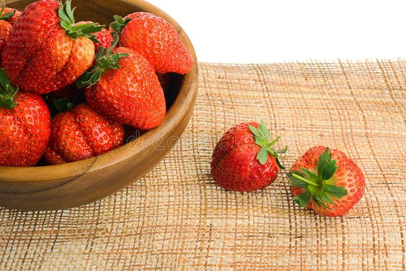 在白色backgro隔绝的木碗的新鲜的成熟草莓 库存图片