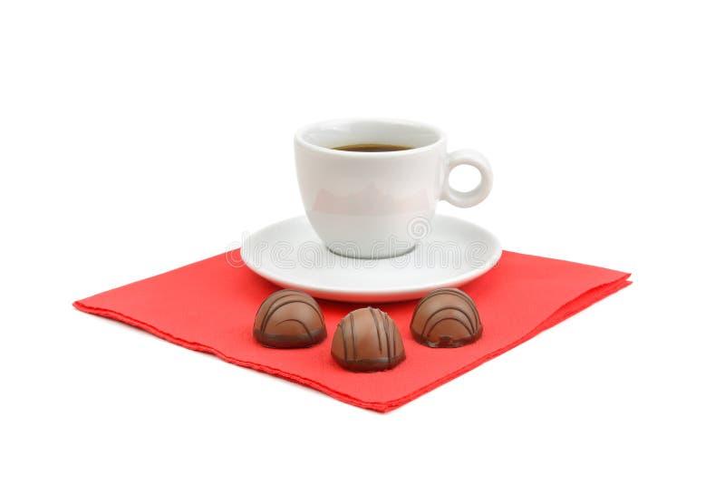 在白色backgrou和巧克力糖隔绝一杯咖啡 免版税库存照片