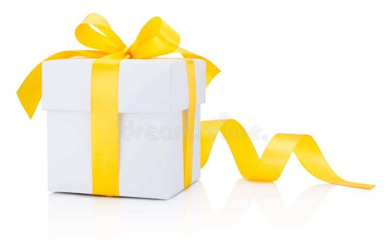 在白色backgrou隔绝的白色礼物盒被栓的黄色丝带弓 免版税库存照片