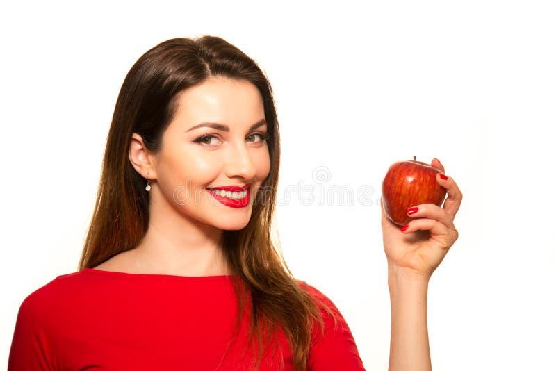 在白色Backgroun隔绝的妇女吃红色苹果计算机果子微笑 库存照片