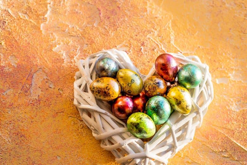 在白色nwst,在黄色背景的心脏的五颜六色的复活节彩蛋 平的位置,顶视图 愉快的复活节 在嵌套的鹌鹑蛋 免版税库存照片