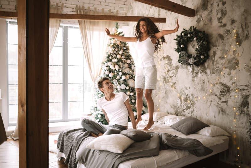 在白色T恤和短裤打扮的愉快的女孩在人旁边坐那里在舒适装饰的床上跳 免版税库存照片