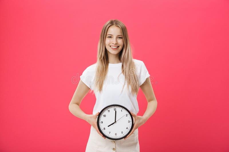 在白色T恤打扮的一激动的少女的画象指向闹钟和看被隔绝的照相机  库存照片