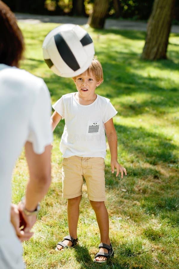 在白色T恤杉打扮的夏时小男孩今后看飞行在他前面的橄榄球球 图库摄影