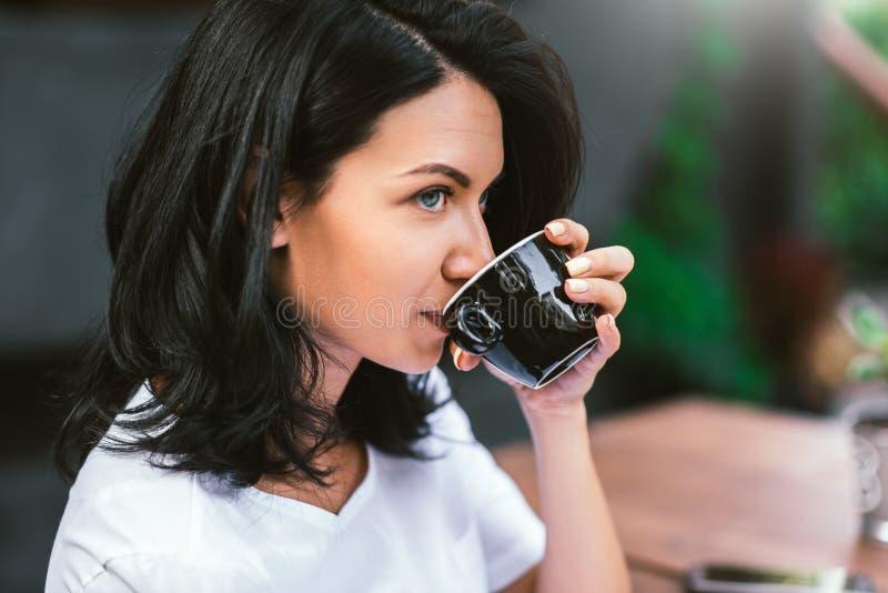 在白色T恤饮用的咖啡打扮的可爱的白种人深色的女孩,看与严肃的沉思表示,做 免版税库存照片