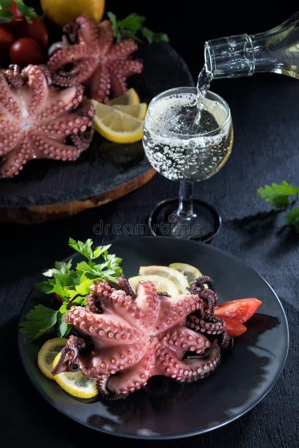 在白酒的被充塞的章鱼用柠檬和蕃茄 Salento,普利亚,意大利章鱼盘  免版税库存图片