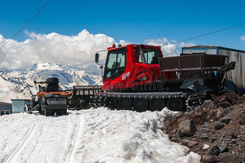 在白雪的红色snowcat运输在山避难所附近清洗滑雪轨道 高加索山脉 库存图片