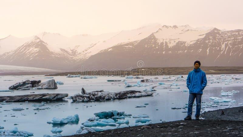 在百万岁前面的亚洲人立场在冰川的冰山 免版税库存照片