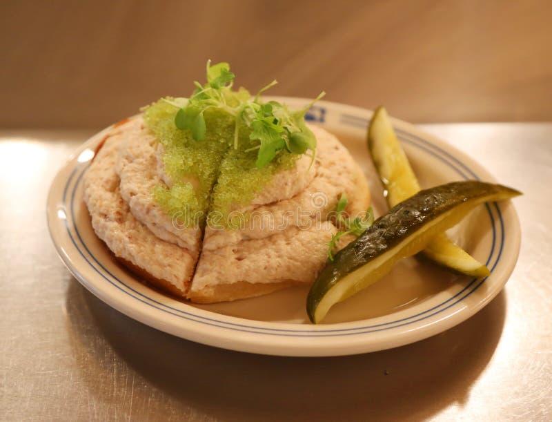 在百吉卷多士的白鲑沙拉与山葵被灌输的鱼獐鹿和腌汁在纽约熟食店服务 库存照片