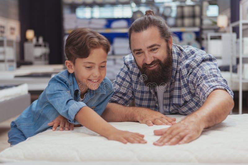 在百货店的愉快的父亲和儿子购物 免版税库存照片