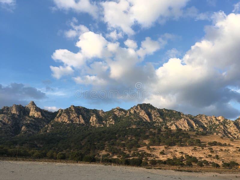 在的云彩晴朗的山 免版税库存照片