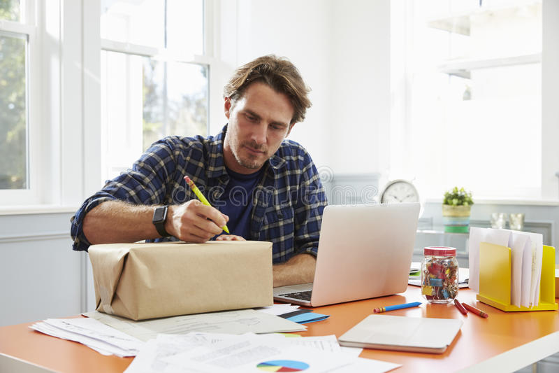在的人在家邮寄的包裹写地址 免版税图库摄影