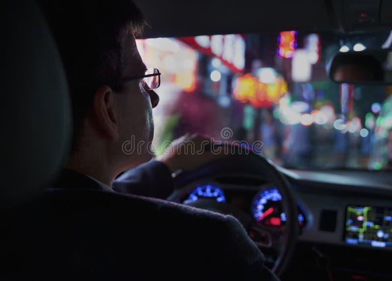 在的商人驾驶在晚上的肩膀观点在城市,有启发性城市点燃 免版税库存图片