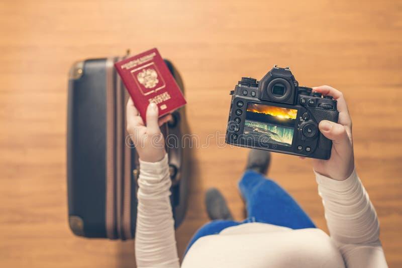 在的女孩的顶视图看起来在她的照相机身分的照片尼亚加拉大瀑布带着手提箱在机场 女孩在家以后回来 库存图片