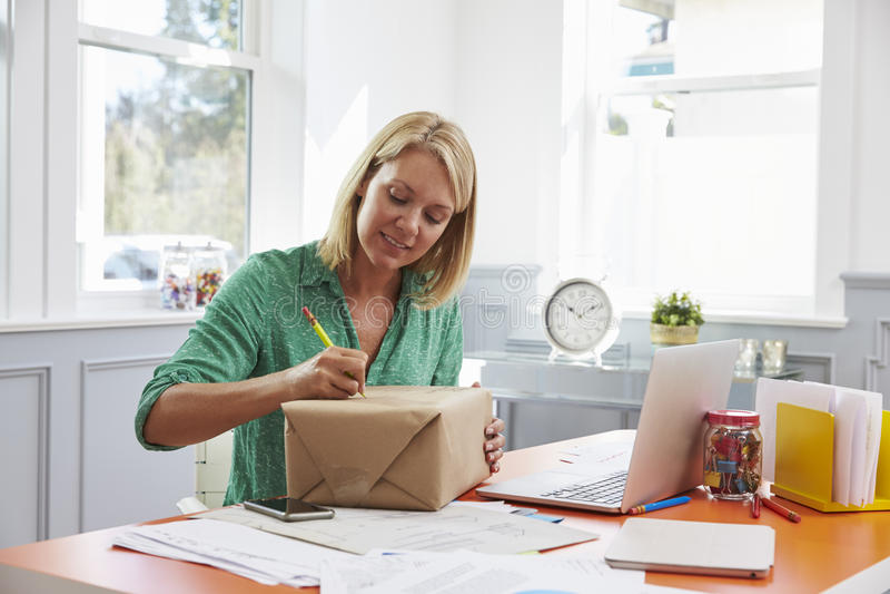 在的妇女在家邮寄的包裹写地址 免版税库存图片