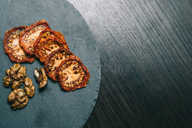在的干蕃茄核桃黑暗的背景 免版税库存照片